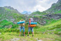 Coppia l'uomo e la donna turistici di viaggiatore con zaino e sacco a pelo del twp con lo zaino Immagini Stock