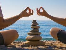 Coppia l'yoga di pratica sulla spiaggia zen La calma e si distende immagine stock