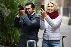 Coppia la camminata con i bagagli, la macchina fotografica e lo smartphone Fotografia Stock Libera da Diritti