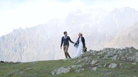 Coppia la camminata sulla nebbia e sui precedenti delle montagne stock footage