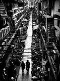 Coppia la camminata in vicolo con il lotto del motociclo Fotografia Stock Libera da Diritti