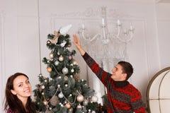 Coppia la collocazione dell'ornamento ultimo su un albero di natale Fotografia Stock