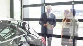 Coppia la conversazione con il capo vendite maturo mentre scelgono un'automobile nella gestione commerciale stock footage