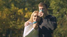 Coppia la degustazione delle bevande calde in parco ed abbracciando, la data romantica, caffè--va stock footage
