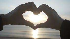 Coppia la fabbricazione della forma del cuore con le loro mani con il tramonto dentro sulla spiaggia al rallentatore - stock footage