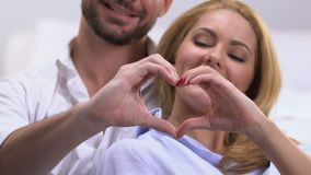 Coppia la fabbricazione il cuore con le mani, il simbolo dell'amore e dell'unità nelle relazioni video d archivio