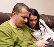 Coppia la lettura sul telefono mobile Fotografie Stock Libere da Diritti