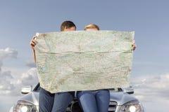Coppia la mappa della lettura mentre si appoggiano il cappuccio dell'automobile durante il viaggio stradale Fotografie Stock Libere da Diritti