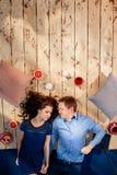 Coppia la menzogne sul pavimento di legno con i cuscini ed i dolci Fotografia Stock