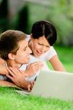 Coppia la menzogne sull'erba verde con il computer portatile d'argento Fotografia Stock Libera da Diritti