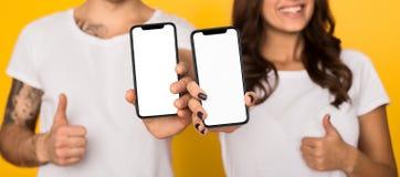 Coppia la mostra degli smartphones con gli schermi in bianco che mostrano il pollice su fotografia stock