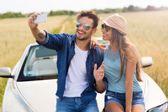 Coppia la presa del selfie mentre fuori su un viaggio stradale Immagine Stock