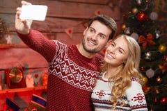 Coppia la presa del selfie sullo smartphone sopra il fondo dell'albero di Natale Immagini Stock