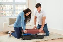 Coppia la prova di chiudere la valigia con a molto copre Fotografie Stock
