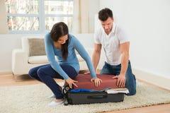 Coppia la prova di chiudere la valigia con a molto copre Immagine Stock