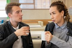Coppia la seduta in caffè con la tazza in mani e la conversazione dispiaciuta fotografie stock