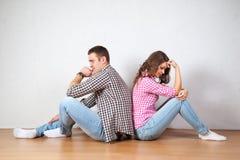 Coppia la seduta con le loro parti posteriori girate dopo avere una discussione Fotografia Stock