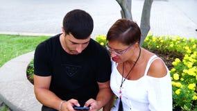 Coppia la seduta sul banco nel giardino e per mezzo della compressa e dello smartphone Stanno esaminando la macchina fotografica stock footage