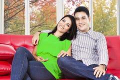 Coppia la seduta sul sofà e sorridere alla macchina fotografica Immagini Stock