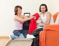 Coppia la seduta sul sofà e sulla valigia d'imballaggio a casa Immagini Stock Libere da Diritti