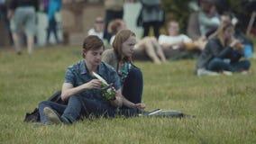 Coppia la seduta sull'erba nel parco ammucchiato della città, mangiatore di uomini stock footage