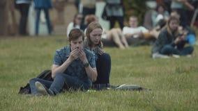 Coppia la seduta sull'erba nel parco ammucchiato della città, uomo che usando il tessuto dopo la cena stock footage