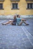Coppia la seduta sulla pavimentazione con le parti posteriori l'un l'altro Immagine Stock Libera da Diritti