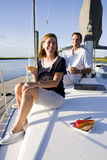Coppia la seduta sulla piattaforma della barca che gode della bevanda Fotografie Stock Libere da Diritti