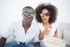 Coppia la seduta sullo strato che guarda insieme il film 3d Immagini Stock