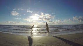 Coppia la siluetta che prende in giro uno un altro sulla spiaggia sabbiosa bagnata archivi video