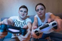 Coppia la simulazione del movimento della direzione del gioco che si siede sul sofà Immagine Stock Libera da Diritti