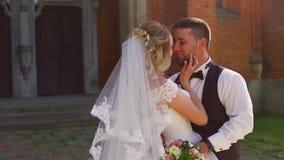 Coppia la sposa e lo sposo sta passeggiando all'aperto sopra la vecchia chiesa video d archivio