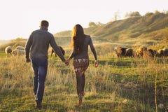 Coppia la tenuta congiuntamente della passeggiata romantica sul prato autunnale Fotografia Stock Libera da Diritti