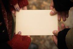 Coppia la tenuta del foglio di carta d'annata vuoto in loro mani immagini stock libere da diritti