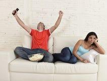 Coppia la TV di sorveglianza per mettere in mostra il calcio con la celebrazione eccitata l'uomo fotografia stock libera da diritti