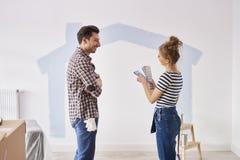Coppia la verniciatura della parete interna in loro nuovo appartamento immagine stock libera da diritti