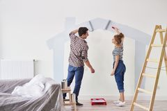 Coppia la verniciatura della parete interna in loro nuovo appartamento immagine stock
