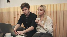 Coppia lavorare al computer portatile, bevente il caffè al caffè Fotografia Stock Libera da Diritti