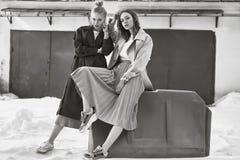 Coppia le belle ragazze dei pantaloni a vita bassa che portano i cappotti lunghi di modo sul Fotografia Stock