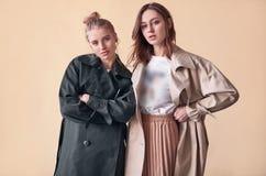 Coppia le belle ragazze dei pantaloni a vita bassa che portano i cappotti lunghi di modo sulla via Fotografie Stock Libere da Diritti