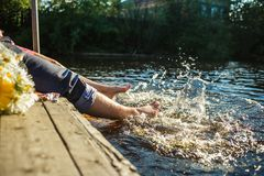 Coppia le gambe nell'acqua che spruzza con il mazzo dei fiori Gioia di estate immagine stock