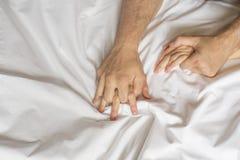 Coppia le mani che tirano gli strati bianchi nell'estasi, orgasmo Concetto di passione Oorgasm Momenti erotici concetto intimo se immagini stock