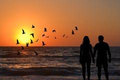 Coppia le siluette che si tengono per mano l'esame dell'alba sulla spiaggia Fotografia Stock Libera da Diritti
