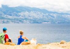 Coppia le viandanti che camminano con il cane alla spiaggia ed alle montagne Fotografia Stock