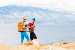 Coppia le viandanti che camminano con il cane alla spiaggia ed alle montagne Fotografia Stock Libera da Diritti