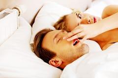 Coppia a letto, donna russante dell'uomo non può dormire Immagine Stock Libera da Diritti