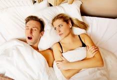 Coppia a letto, donna russante dell'uomo non può dormire Immagine Stock