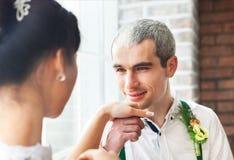 Coppia sposata allegra che sta vicino al muro di mattoni Immagini Stock