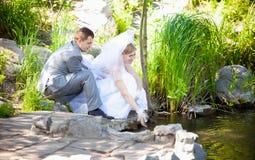 Coppia sposata che si siede sulla riva e sull'acqua commovente Immagini Stock