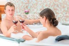 Coppia sposata con i bicchieri di vino nella Jacuzzi Fotografie Stock